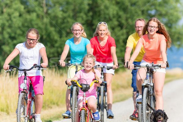 Család biciklik kosz út lovaglás lefelé Stock fotó © Kzenon