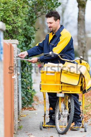 Postman riding his cargo bike carrying out mail Stock photo © Kzenon