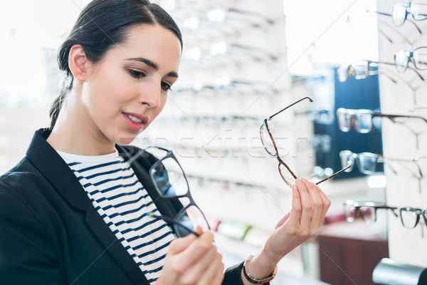 Woman comparing glasses at optician Stock photo © Kzenon