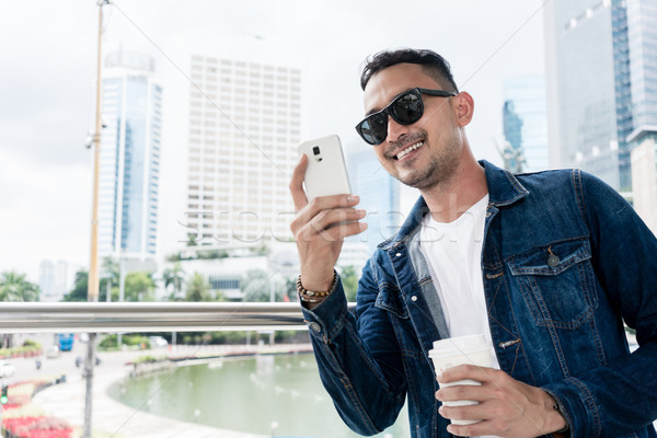 Trendy young man smiling during online communication on his smar Stock photo © Kzenon