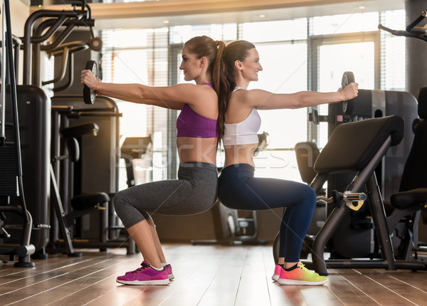 Two young women exercising together back to back with weight pla Stock photo © Kzenon