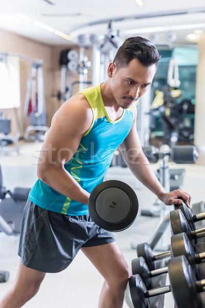 Portrait of a handsome young man exercising bicep curls during u Stock photo © Kzenon