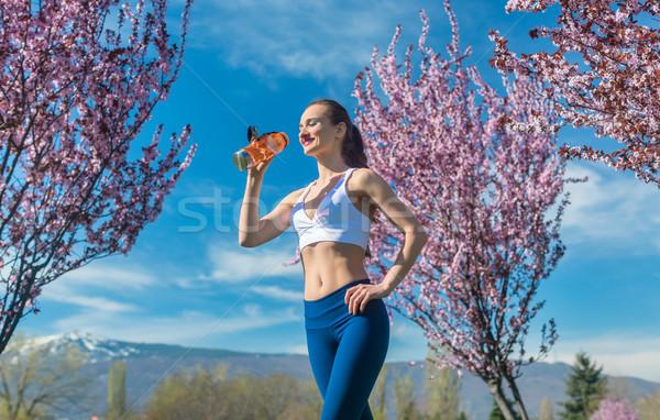 Woman having break from running drinking water Stock photo © Kzenon