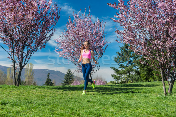 Woman doing sport running on hill between blossoming cherry trees Stock photo © Kzenon