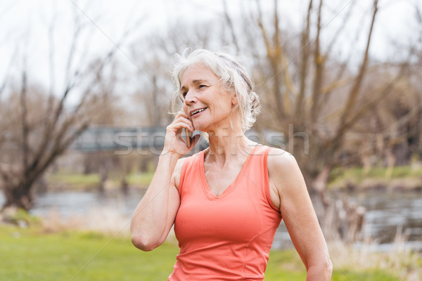 Senior woman in sport clothes receiving call on her mobile phone Stock photo © Kzenon