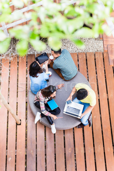 Young employees using modern wireless technology while working outdoors Stock photo © Kzenon