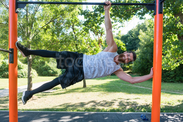 Muscular young man doing bodyweight exercises in a modern fitness park Stock photo © Kzenon