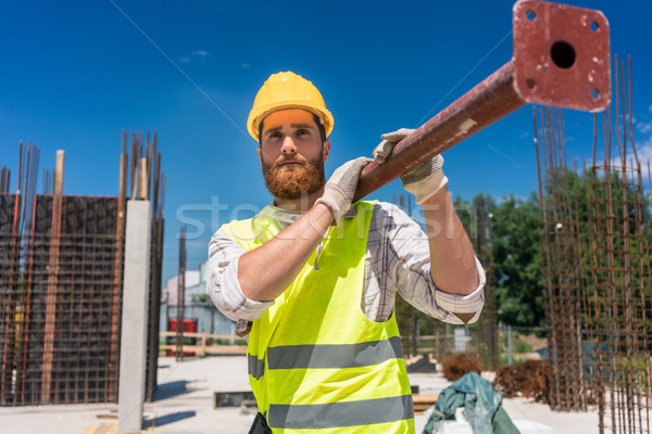 Blue-collar worker carrying a heavy metallic bar during work Stock photo © Kzenon