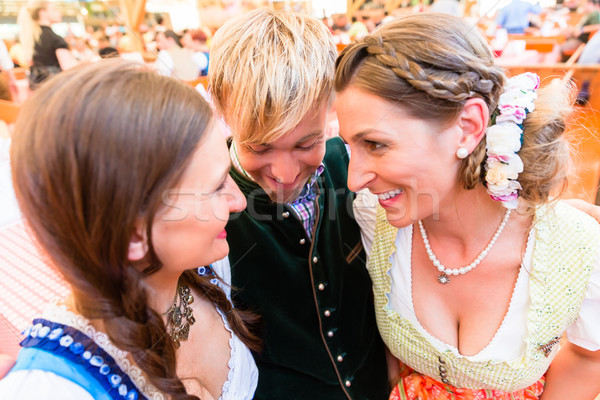 Man hugging two dirndl wearing women in Bavarian beer tent Stock photo © Kzenon