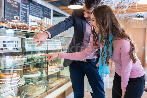 Beautiful young woman showing a layered cake to her boyfriend Stock photo © Kzenon