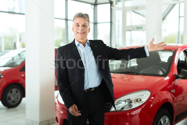 Mature man with auto in car dealership Stock photo © Kzenon