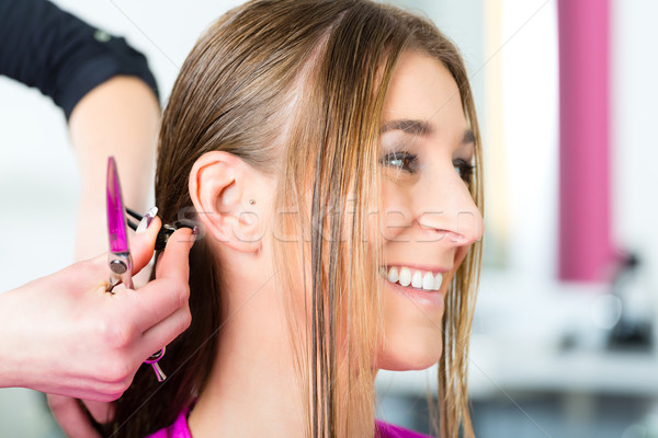 Woman receiving haircut from hair stylist or hairdresser Stock photo © Kzenon