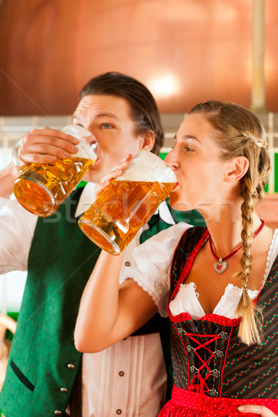 Stock photo: Man and woman with beer glass in brewery