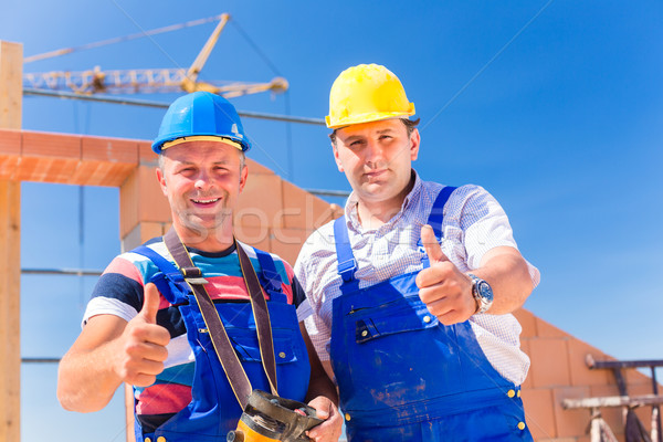 Construction site workers building walls on house Stock photo © Kzenon