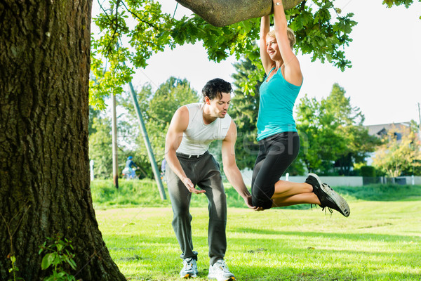 People in city park doing chins or pull ups on tree Stock photo © Kzenon