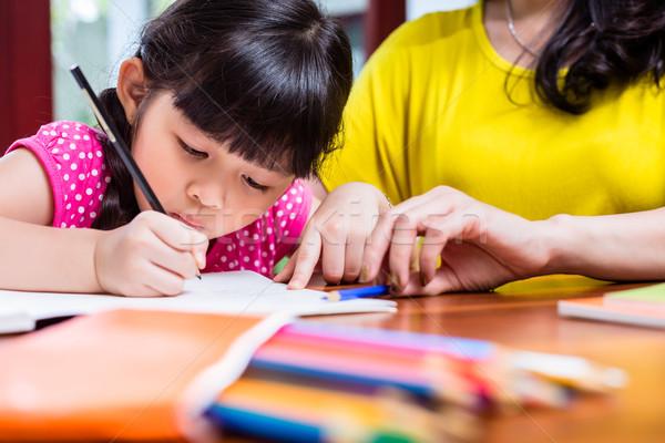 Chinese mother homeschooling her child Stock photo © Kzenon