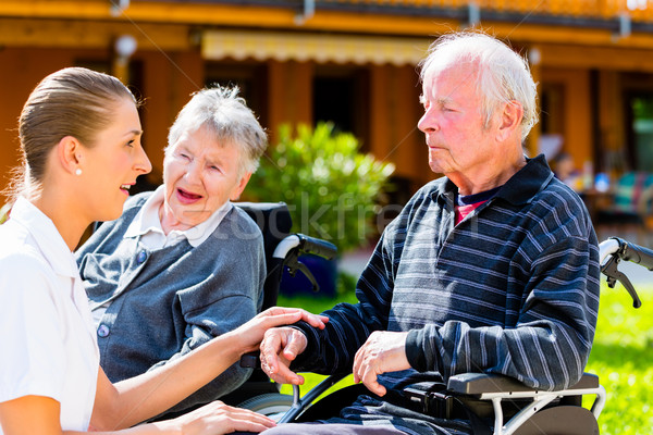 Seniors eating candy in garden of nursing home Stock photo © Kzenon