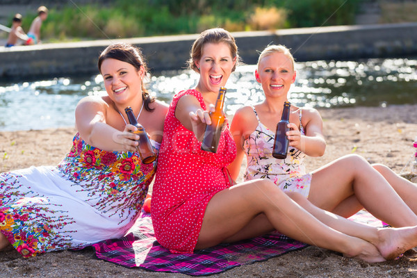 Friends drinking beer at river beach Stock photo © Kzenon
