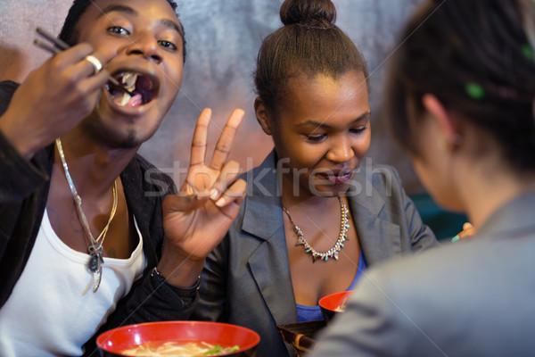 Groep jonge zwarte mensen dining asian restaurant Stockfoto © Kzenon
