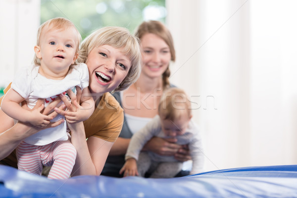 Stock photo: Young moms and their little children in mother and child course