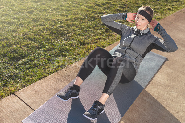 Young woman doing crunches for the abdominal muscles outdoors in Stock photo © Kzenon
