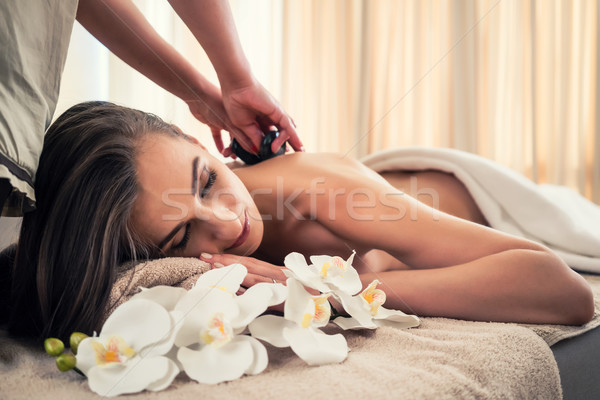 Young woman receiving hot stone massage at spa and wellness cent Stock photo © Kzenon
