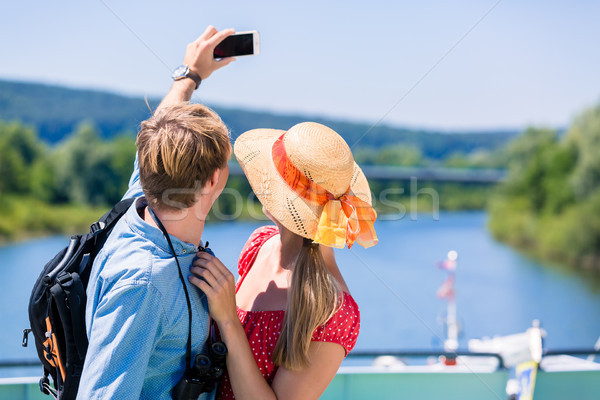 Young couple on river cruise in summer taking selfie Stock photo © Kzenon