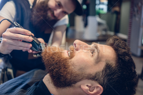Close-up of the head of a man and the hand of a barber trimming  Stock photo © Kzenon