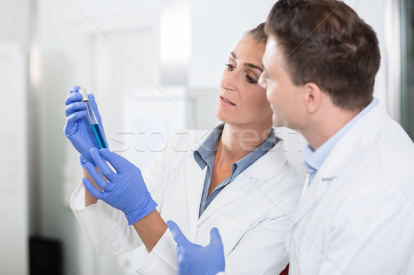 Scientists in laboratory looking at blue liquid in vial  Stock photo © Kzenon
