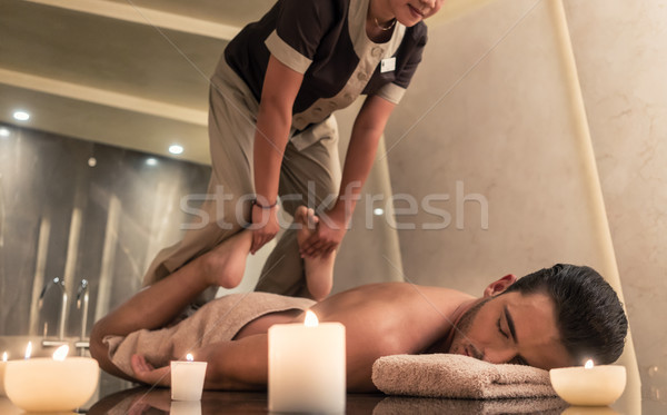 Thai massage practitioner massaging man through stretching techn Stock photo © Kzenon