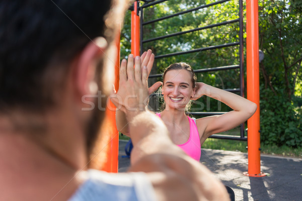 Cheerful young woman giving high-five to her partner while doing Stock photo © Kzenon