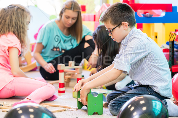 Pre-school boy cooperating with kids under guidance of kindergar Stock photo © Kzenon