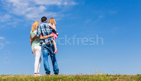 Parents and daughter, arm in arm in back view Stock photo © Kzenon