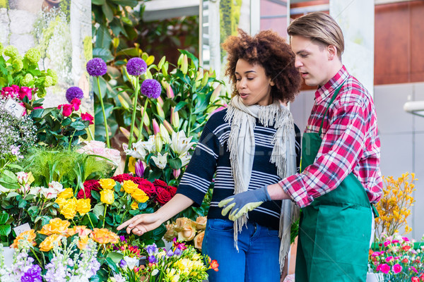 Beautiful woman buying freesias at the advice of a helpful vendo Stock photo © Kzenon