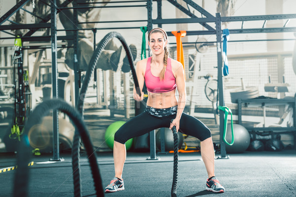 Full length of a strong and beautiful woman waving battle ropes  Stock photo © Kzenon