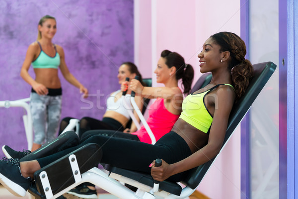 Young woman doing exercise for legs while attending group class  Stock photo © Kzenon