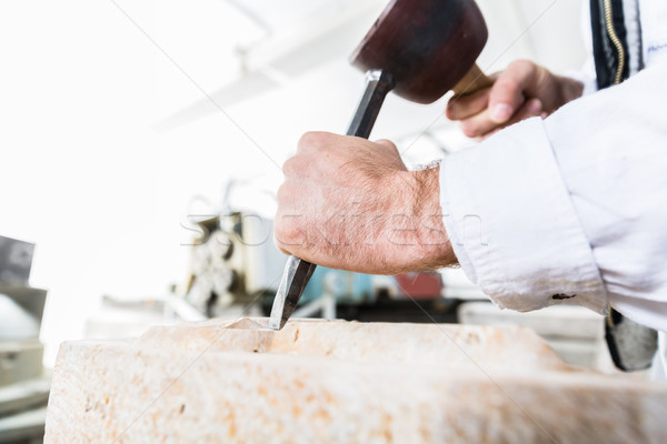 Stonemason cutting boulder with hammer and chisel Stock photo © Kzenon