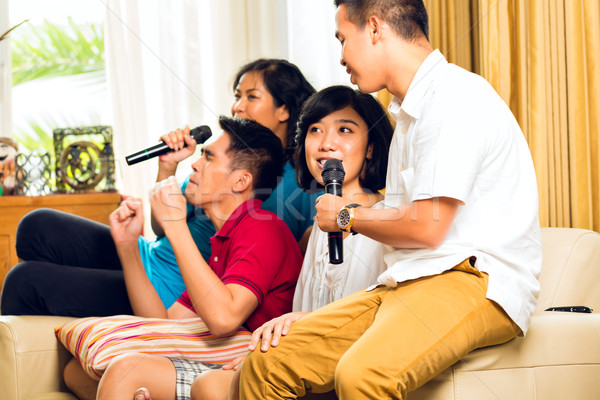 Asian people singing at karaoke party Stock photo © Kzenon