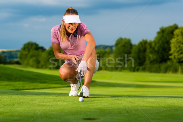 Young female golf player on course aiming for her put Stock photo © Kzenon