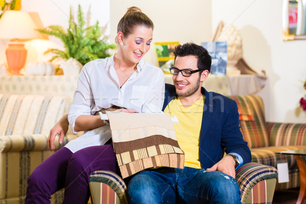 Couple picking armchair seat cover in furniture store Stock photo © Kzenon