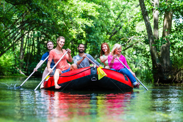 Stock photo: Friends paddling on rubber boat at forest river or creek