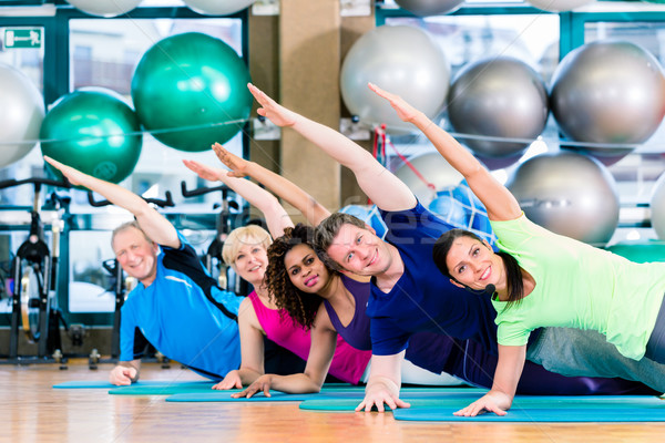 Gymnastic group in gym exercising and training Stock photo © Kzenon