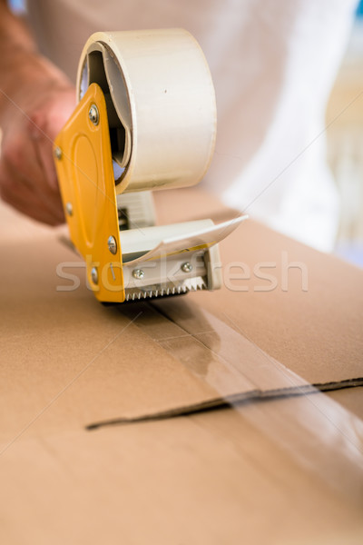 Man taping packing case Stock photo © Kzenon