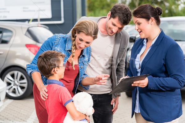 Car dealer advising family on buying auto Stock photo © Kzenon