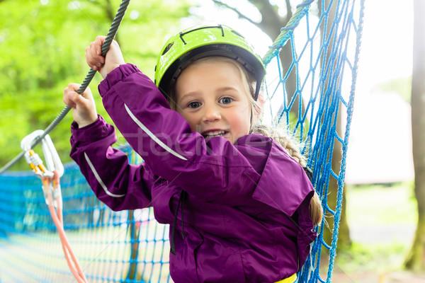 Girl climbing in high rope course Stock photo © Kzenon