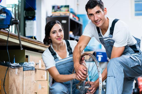 Woman and man as bike mechanics in workshop Stock photo © Kzenon
