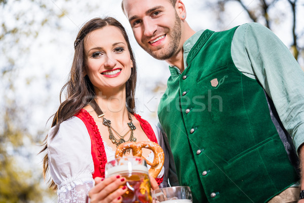 Couple in Dirndl and Tracht having Pretzel and Bier  Stock photo © Kzenon
