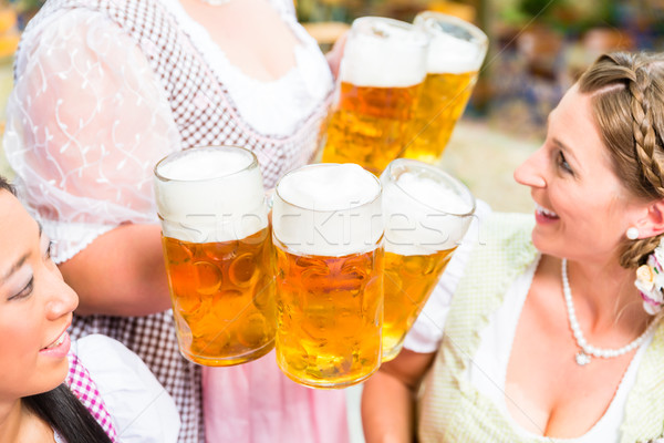 Waitress serving beer in five beer glasses Stock photo © Kzenon