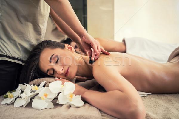 Woman enjoying traditional hot stone massage next to her partner Stock photo © Kzenon