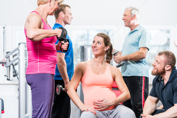 Stock photo: Pregnant woman with senior people working out at the gym with pe